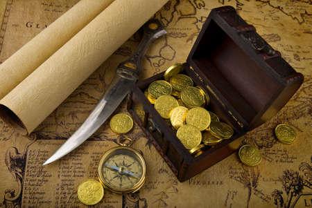 schatkaart: Oude koperen kompas, liggend op een zeer oude kaart met schat kist vol gouden munten  Stockfoto