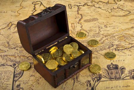 a rare: Very old map with treasure chest full of golden coins on a vintage map Stock Photo