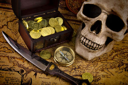 Pirae treasure. Old brass compass lying on a very old map with treasure chest full of golden coins, skull and knife photo