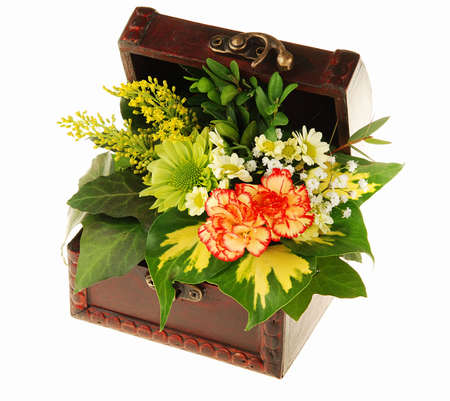 Old wooden open chest full of various flowers isolated on white photo