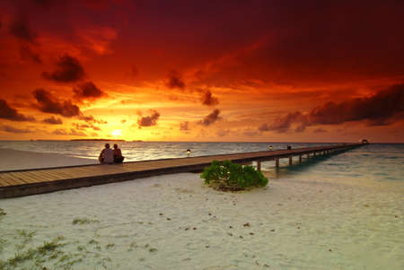 Romantic couple sitting on the jetty in the Maldives at sunset Stock Photo