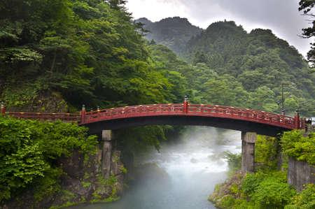 ponte giapponese: Ponte rosso di sacro Shinkyo in Nikko, Giappone e una nebbia in aumento dal fiume