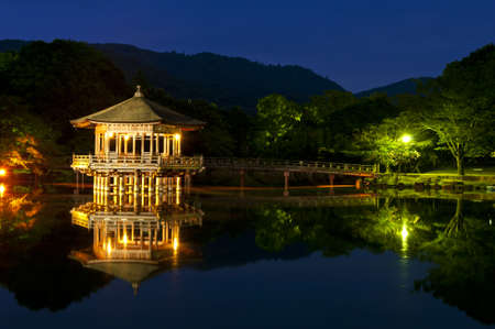 Nice japanese wooden gazebo is shortly after the sunset reflecting in the water. Nara, Japan. photo