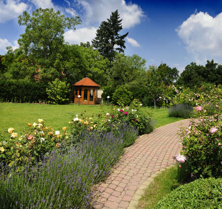 garden path: Beautiful garden with blooming roses, brick path and a small gazebo Stock Photo