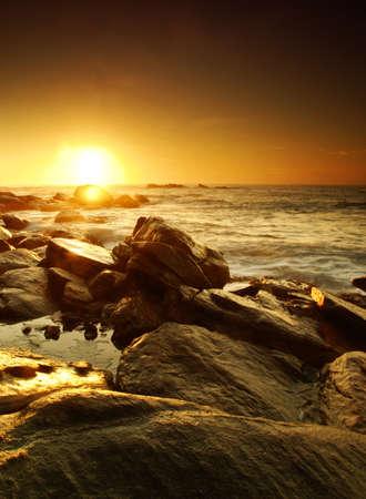 Beautiful colorful sunset over sea and boulders on Sri Lanka photo