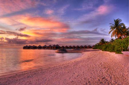 Bellissimo tramonto sulla spiaggia con vivaci le ville acqua nell'oceano Indiano, Maldive