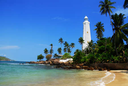 Beautiful white lighthouse Dondra Head, the southest cape of Sri Lanka - seen from the beach. The lighthouse is also a highest (161 feet) not only on the island but also in the whole Asia Stock Photo - 10013914