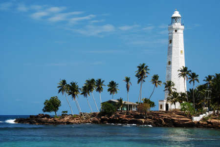 Beautiful white lighthouse Dondra Head, the southest cape of Sri Lanka - seen from the beach. The lighthouse is also a highest (161 feet) not only on the island but also in the whole Asia Stock Photo - 10428771
