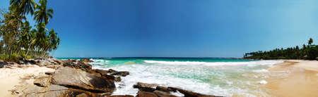 blue lagoon: Ampia foto panoramica di una bella spiaggia tropicale con rocce e palme. Tangalla, Sri Lanka