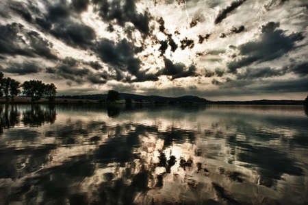 tonality: Very dramatic sunset is being reflected in the large lake. Dark deep tonality, HDR