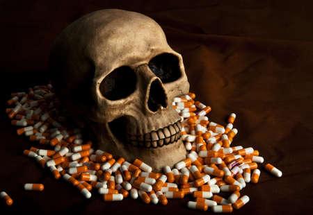 sobredosis: Cráneo dramática en la pila de drogas simboliza la enfermedad y el peligro de abuso