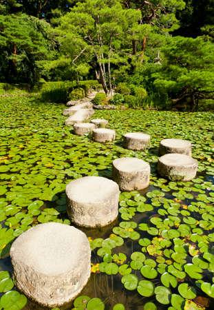 平安 Shrine.Stones 近くの日本庭園で禅石のパスは蓮の葉に囲まれています。