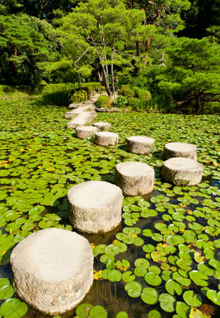 Zen stenen pad in een Japanse tuin nabij Heian Shrine.Stones zijn omgeven door lotus bladeren