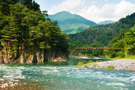ogimachi: Beautiful landscape in the Japanese mountains with a wild river, red bridge and rock covered by typical pines Stock Photo