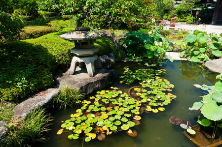 Beautiful Japanese garden with a lake and a lantern in the front photo