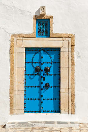 Beautiful ornamental blue door of so typical shape for Tunisia  photo