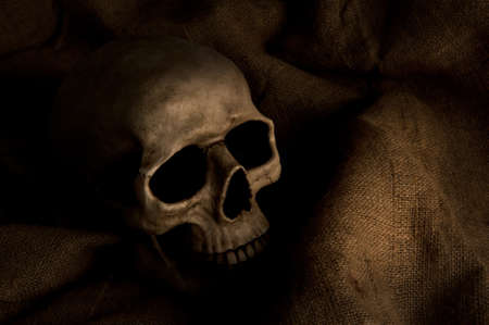 Scary dimly lit human skull laying on the gunny cloth photo