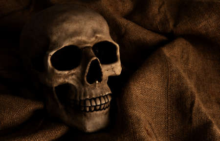 dimly: Scary dimly lit human skull laying on the gunny cloth