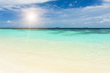 Beautiful crystal clear Maldivian sea and a blue sky with a sun photo
