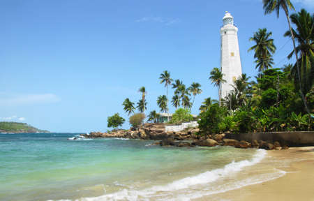 Beautiful white lighthouse Dondra Head, the southest cape of Sri Lanka - seen from the beach. The lighthouse is also a highest (161 feet) not only on the island but also in the whole Asia Stock Photo - 11425349