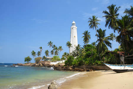 Beautiful white lighthouse Dondra Head, the southest cape of Sri Lanka - seen from the beach. The lighthouse is also a highest (161 feet) not only on the island but also in the whole Asia photo