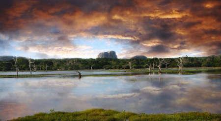 yala: Beautiful sunset over the lake and Elephant rock in the Yala national park, Sri Lanka Stock Photo