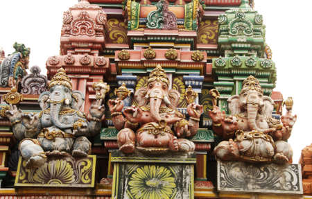 Detail of beautiful hindu temple with a Ganesha (elephant deity) statues isolated on white photo