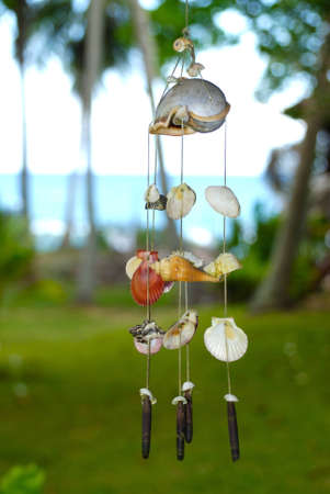 wind chime: Windchime made of shells against the blurred backround of a tropical sea and a palm grove Stock Photo