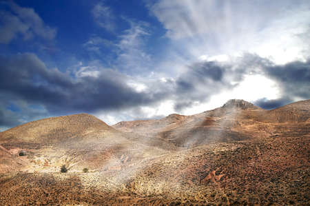 Not only sand dunes, but also arid mountains are a face of mighty desert Sahara. Here with dramatic sky after the storm Stock Photo - 13180940