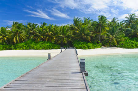 Tropical Maldivian paradise - a jetty leading to a beautiful tropical atoll hiden in the azure Indian ocean.
