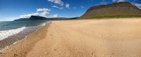Beach under the mighty fjords rising from the sea in the Westfjords Peninsula, northwestern Iceland photo
