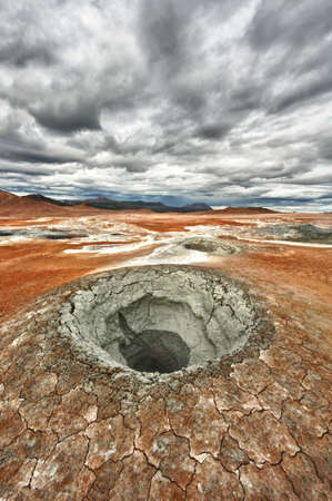 Mudpot in the geothermal area Hverir, Iceland. The area around the boiling mud is multicolored and cracked photo