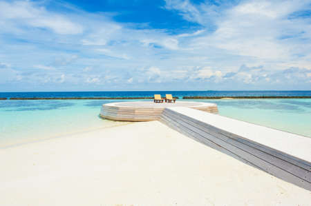 Two deck chairs on the wooden foothpath in the Maldives photo