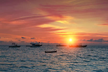 Vivid sunset over the harbor in the Maldives photo