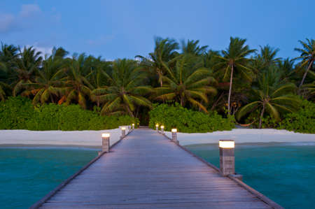 ari: Tropical Maldivian paradise - a jetty leading to a beautiful tropical atoll hiden in the azure Indian ocean. Evening shot.