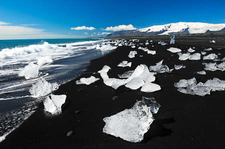 Beautiful beach in the South of Iceland with a black lava sand is full of icebergs from glaciers not far away photo