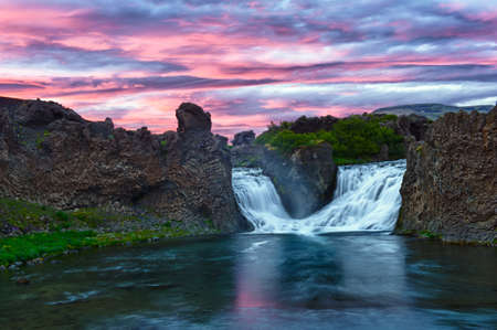 after midnight: Double waterfall Hjalparfoss on the river Fossa after the midnight sunset with a beautiful vivid dramatic sky and basalt rocks