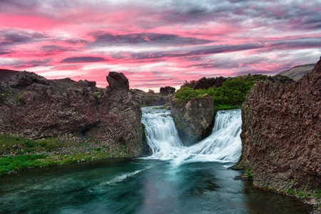 iceland: Double waterfall Hjalparfoss on the river Fossa after the midnight sunset with a beautiful vivid dramatic sky and basalt rocks