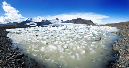 Beautiful panoramic of Fjallsarlon Glacial lake full of floating icebergs near the Fjallsjokull glacier photo