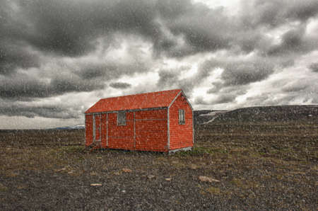 Old red snowstorm shelter can save a life in a cruel blizzard or in winter on Iceland photo