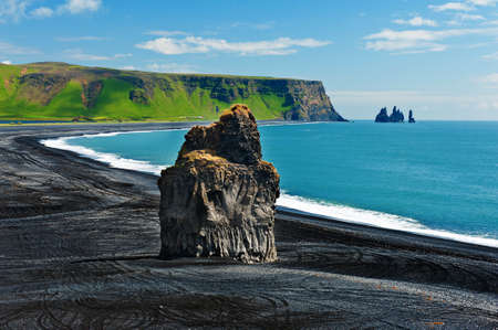 Beautiful rock formation on a black volcanic beach at Cape Dyrholaey, the most southern point of Iceland.