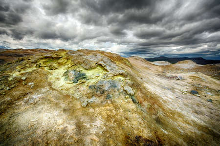 the stinking: Fumarole in the geothermal area Hverir, Iceland. The area around is multicolored and cracked.  Stock Photo
