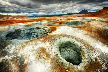Mudpot in the geothermal area Hverir, Iceland. The area around the boiling mud is multicolored and cracked. HDR image