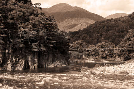 Beautiful landscape in the Japanese mountains with a wild river, red bridge and rock covered by typical pines. Tobacco tint photo