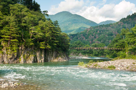 Beautiful landscape in the Japanese mountains with a wild river, red bridge and rock covered by typical pines photo