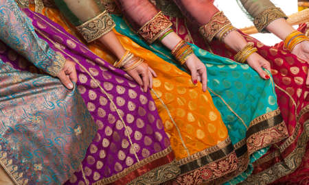 wristlet: Bollywood dancers are holding their vivid costumes. Hands are in a row