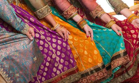 Bollywood dansers houden hun levendige kostuums. Handen zijn op een rij