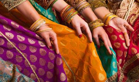 sari: Bollywood dancers are holding their vivid costumes. Hands are in a row