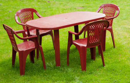 Big red plastic tabler with four chairs standing on the green lawn photo