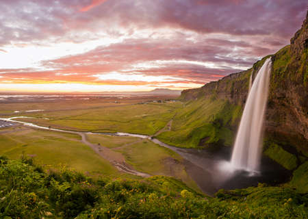 Seljalandsfoss is one of the most beautiful waterfalls on the Iceland. It is located on the South of the island. This photo is taken during the incredible sunset at approx. 1 AM.  photo